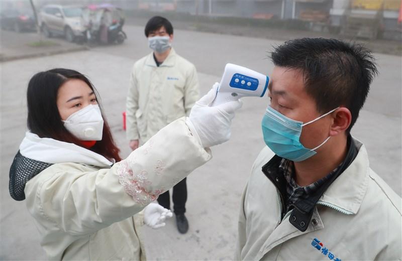 中國官方通報,截至13日,中國大陸武漢病毒肺炎累計確診病例達6萬3851例,累計死亡1380例。圖為四川電子公司的防疫人員替員工測量體溫。(中新社提供)