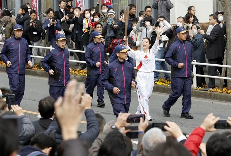 東京奧運組委會15日彩排傳遞聖火,參與女星石原聰美(白衣者)表示,相信奧運將留下很多好回憶。(共同社提供)