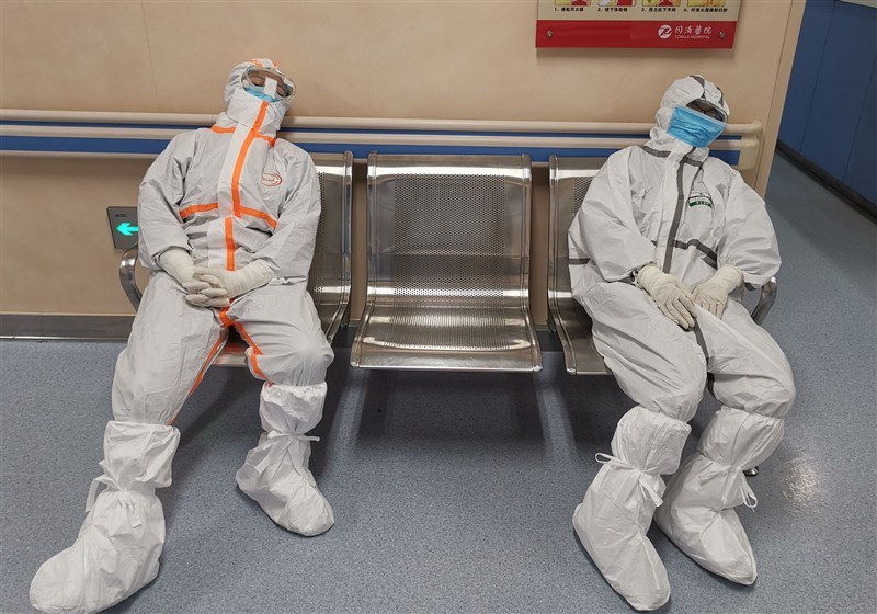 中國湖北省官員表示,對抗致命武漢肺炎疫情的中國第一線醫護人員子女,將能在申請學校及高等教育的考試中加分。圖為湖北同濟醫院兩名醫護人員在病房外的椅子上休息。(中新社提供)