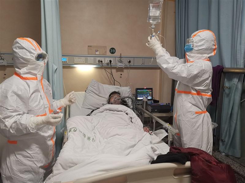中國國家衛生健康委員會官網通報,湖北以外地區的新增確診病例,20日暴增至478例,比湖北通報的411例還多。圖為湖北同濟醫院醫護人員為武漢肺炎患者治療。(中新社提供)