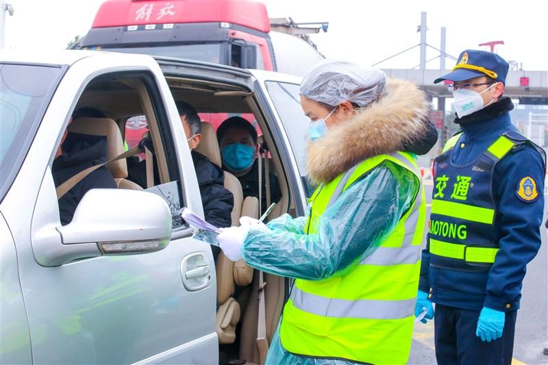 武漢疫情防控指揮部24日朝令夕改,上午允許部份人員離境的通告下午就撤銷,引起質疑。圖為江蘇省交警在重要關口對通過車輛人員登記、量體溫。(中新社提供)