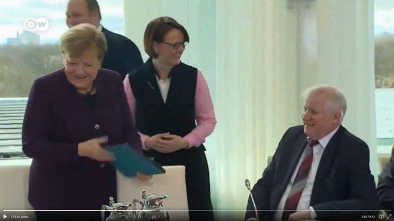 德國總理梅克爾(前左1)2日在一場會議開始前,向內政部長賽賀佛(右1)打招呼並伸出手去,賽賀佛展露笑容但並未相應伸手。(圖取自twitter.com/dw_politics)