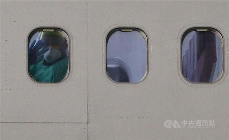 台灣派出包機接回日本郵輪鑽石公主號上台籍旅客及先遣醫師,2月21日晚間順利返台,機內穿著隔離衣的旅客透過機窗向外揮手致意。中央社記者邱俊欽桃園機場攝 109年2月21日