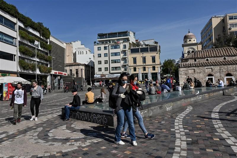 台灣一名高中生1月與家人同遊希臘,出國很久,3月5日返台,15日確診2019冠狀病毒疾病,達停課標準。圖為14日希臘雅典有遊客戴上口罩防疫。(法新社提供)