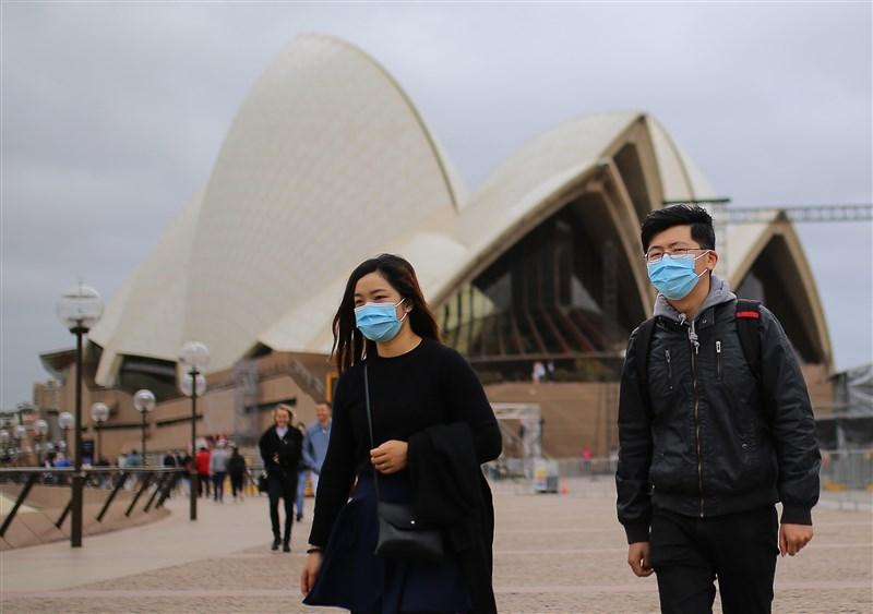 紐西蘭總理阿爾登14日表示,正努力敲定必要的防疫邊境檢疫措施,盼2021年4月前能實施雙邊免隔離的「旅行泡泡」,恢復紐澳間的旅行。圖為雪梨歌劇院前民眾戴上口罩。(安納杜魯新聞社)