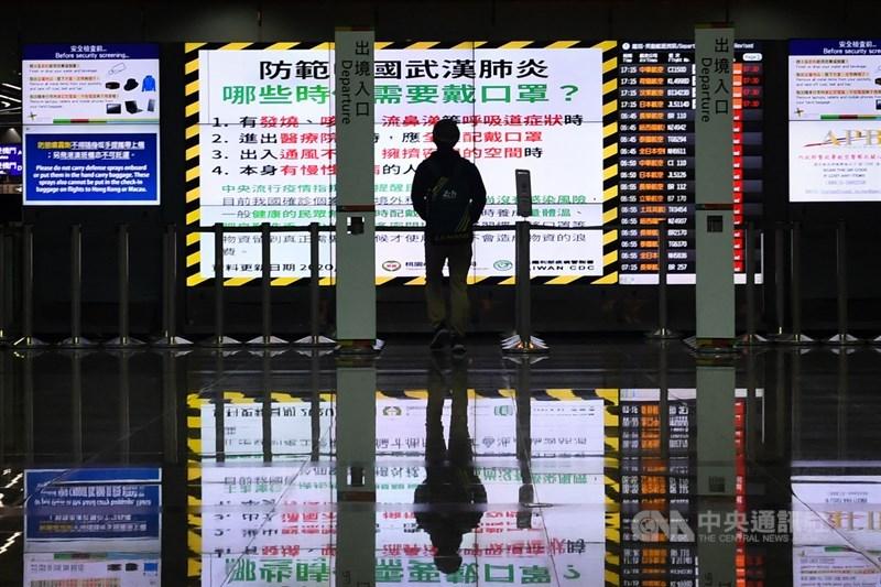 受到武漢肺炎疫情影響許多班機取消,桃園國際機場22日出境大廳空蕩,一名民眾站在電子看板前觀看疫情警語。中央社記者林俊耀攝 109年3月22日