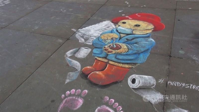 受疫情影響,17日在倫敦特拉法加廣場,地上的塗鴉呼應時事,帕丁頓熊戴上口罩,洗著熊掌。中央社記者戴雅真倫敦攝 109年3月19日