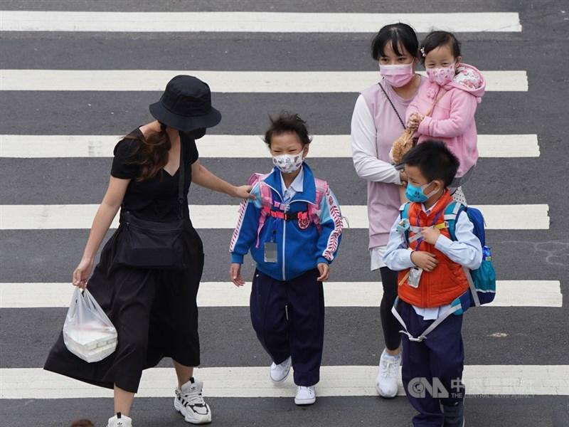 副總統陳建仁23日在臉書分析目前各國武漢肺炎疫情仍處上升階段,待緩和至少還需兩個月時間。圖為北市家長帶孩童外出,為他們戴好口罩。中央社記者徐肇昌攝 109年3月23日