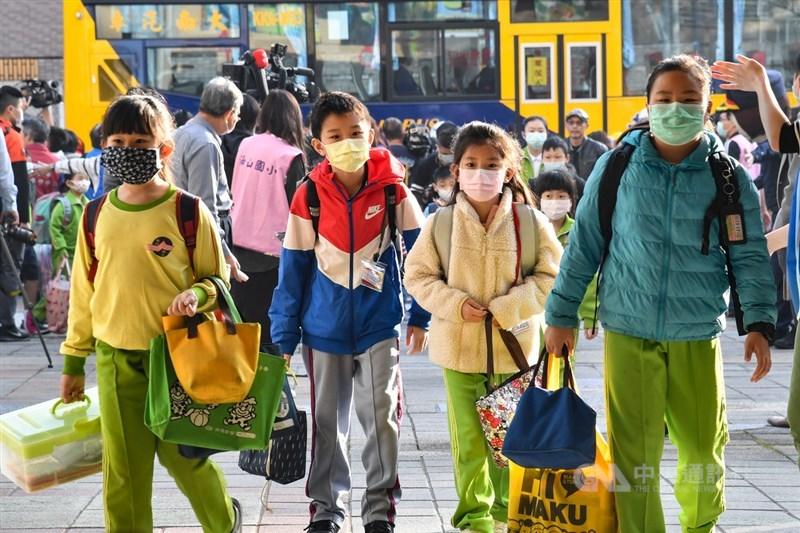 目前有超過160個國家已經勒令學校關閉,全球近9成學生不用上課,然而台灣、新加坡、澳洲的學校都仍正常上課,截然不同的表現吸引外媒撰文討論。圖為學童戴口罩上學。(中央社檔案照片)