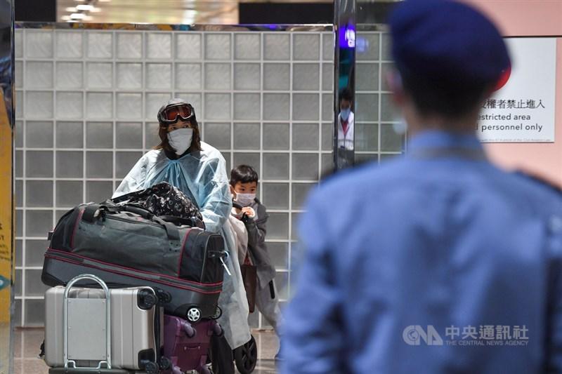 中央流行疫情指揮中心自3月19日宣布,入境一律居家檢疫14天,居家檢疫人數大幅上升。圖為桃園國際機場旅客返台,一名家長戴護目鏡和口罩與小孩入境。中央社記者林俊耀攝 109年3月22日