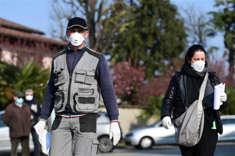 法新社彙整的官方紀錄顯示,截至台灣5日晚間7時,全球感染武漢肺炎死亡人數增至6萬5272例。圖為義大利民眾戴口罩防疫。(法新社提供)