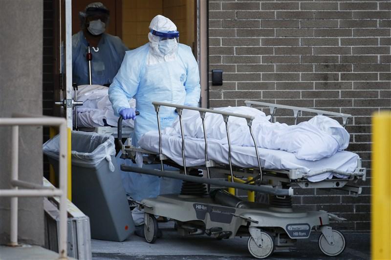 截至6日,紐約武漢肺炎的死亡病例攀升至3485起。在此之際,穿著防護衣的醫護人員運送擔架上蓋著白布的遺體,成為各家醫院外頭常見的景象。(美聯社)