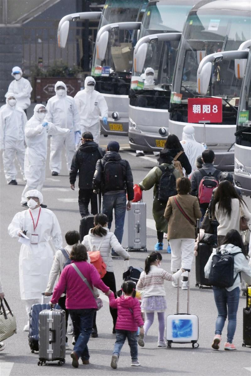 中國官方自2月開始對內對外皆宣傳武漢肺炎防控有成,試圖以大外宣扭轉「疫情源頭」印象。圖為武漢解封後民眾出城抵北京,由穿戴全副隔離裝備的防疫人員引導方向。(共同社提供)