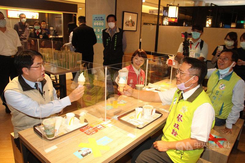 台南市長黃偉哲(前左)21日到新光三越台南新天地視察消毒清潔情形,與同行的台南市議員蔡旺詮(前右)等人在設有隔板的公共用餐區吃冰淇淋,示範安全用餐距離。中央社記者楊思瑞攝  109年4月21日