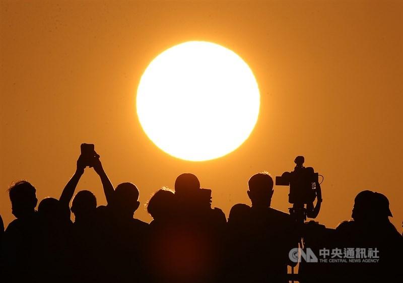 台北市4月30日到5月4日傍晚在無雲遮擋下出現懸日美景,不少「攝手」卡位搶拍。中央社記者張新偉攝 109年4月29日
