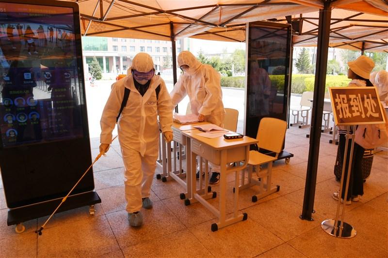 中國東北疫情加劇,12日全中國新增確診7例,其中本土6例集中在吉林省。圖為7日吉林省長春中醫藥大學復學報到處消毒。(中新社提供)