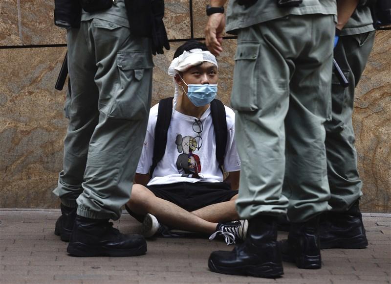 中國企圖推「港版國安法」引發高度爭議,美國國務卿蓬佩奧27日向美國國會認證,香港不再擁有高度自治,因此不再符合美國法律下特殊待遇。圖為香港立法會27日恢復二讀辯論「國歌條例草案」,港警與議會外抗議民眾對峙。(美聯社)