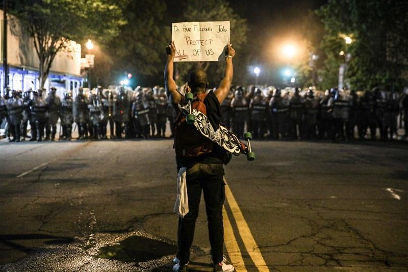 全美各地掀起抗議警察暴力示威潮,儘管許多城市已實施宵禁和動員國民兵,失控的動亂仍不見平息。圖為華盛頓一名示威者手舉標語抗議。(安納杜魯新聞社提供)