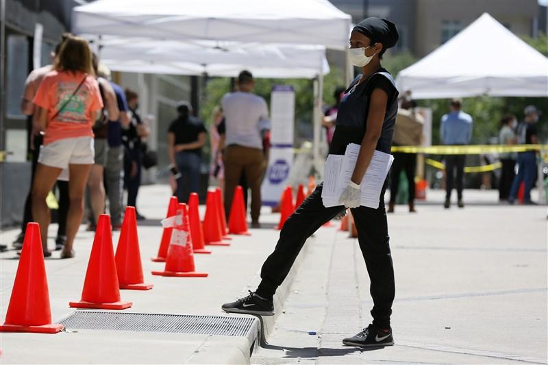 全美50州陸續放寬社交距離、恢復商業活動後,人口眾多的德州和佛羅里達本週雙雙通報2019冠狀病毒疾病單日新增病例攀新高。圖為德州達拉斯民眾排隊篩檢。(美聯社)
