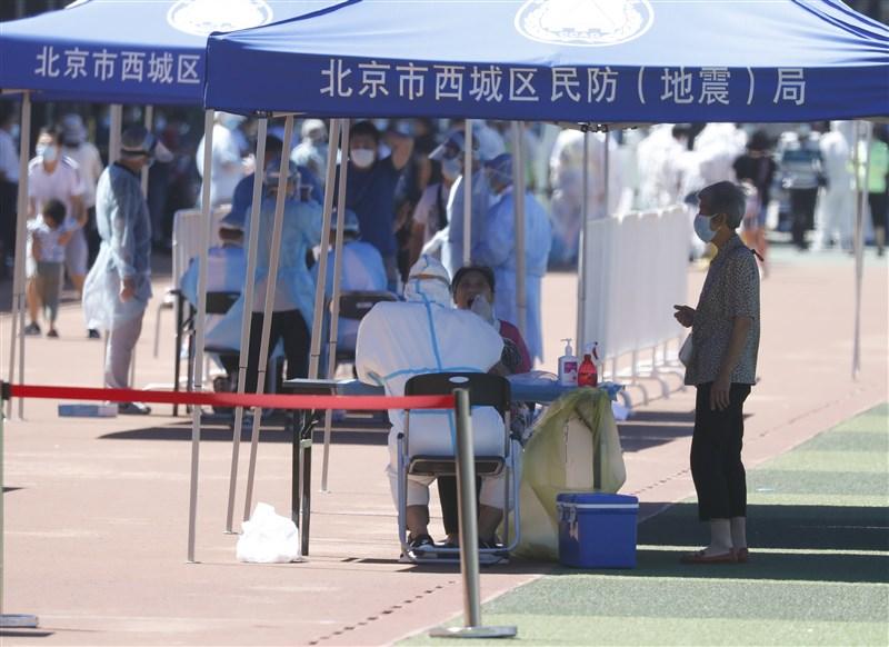 北京一名女子近日外出用餐時,接獲武漢肺炎檢測陽性的通知後情緒崩潰,隨後被送醫。圖為6月14日北京市民在一處體育場接受採檢。(中新社提供)