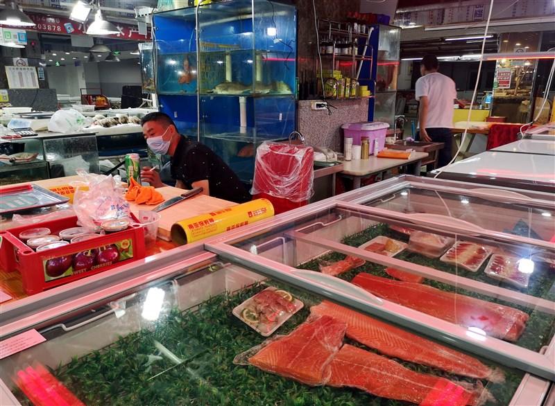 北京傳出在鮭魚砧板上驗出歐洲的武漢肺炎病毒株,病毒專家張上淳表示,病毒透過魚傳播機會小,比較可能是隱藏的確診個案造成環境汙染。圖為北京立水橋海鮮市場。(中新社提供)
