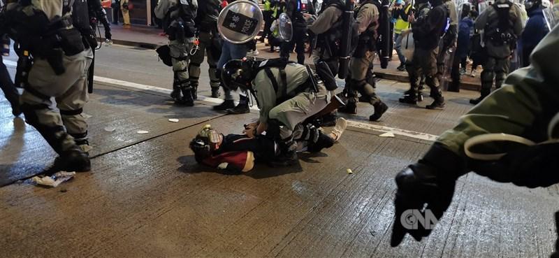 中國全國人大常委會30日通過「港區國安法」,港台引述消息表示,法例沒有提及追溯力,但過往2年從事危害國家安全的人繼續涉嫌犯事,曾涉嫌犯事的證據可能成為法庭上的舉證參考。圖為1月香港遊行港警逮捕示威者。(中央社檔案照片)