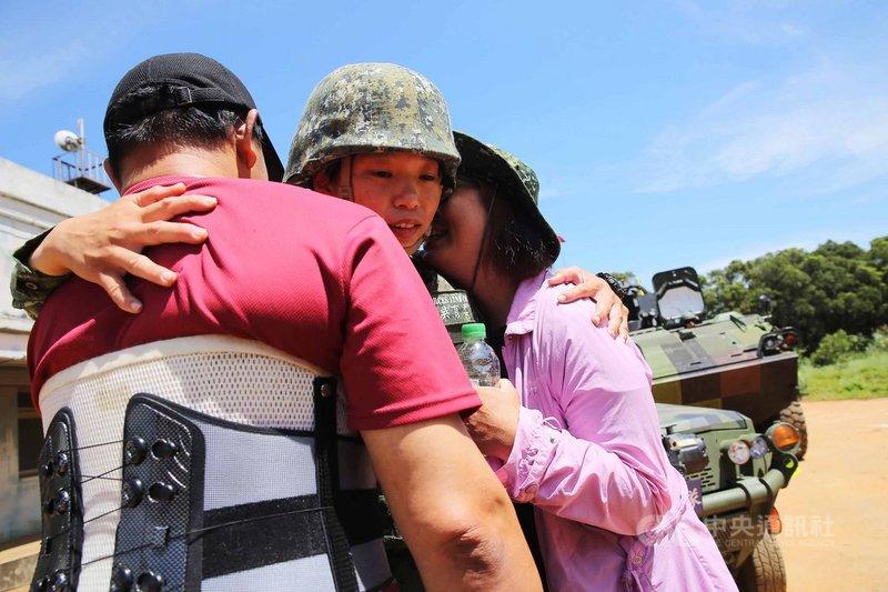 特一營特二連女性少尉輔導長吳育柔(中)19日進行行軍演練,訓後父母親突然現身打氣,3人相擁,成為最美風景。中央社記者游凱翔攝  109年6月19日