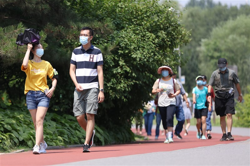 中國21日新增11例武漢肺炎本土確診病例,包括北京9例和與之相關的河北2例。圖為北京民眾21日戴口罩在北京奧林匹克森林公園散步。(中新社提供)