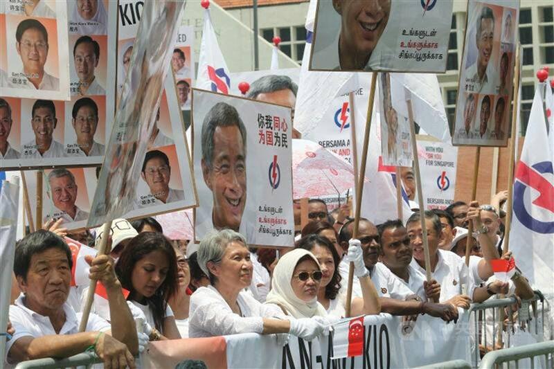 新加坡總統哈莉瑪23日接受總理李顯龍的建議解散國會,確定下屆國會大選提名日是6月30日,並在7月10日大選。圖為2015年新加坡大選提名日,人民行動黨的群眾熱情舉牌支持新加坡總理李顯龍。(中央社檔案照片)