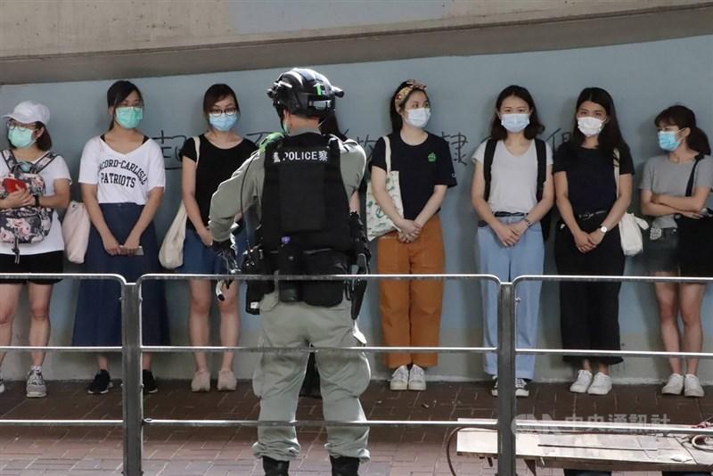 「港區國安法」6月30日深夜生效後,許多港人7月1日走上街頭遊行抗議。由於遊行未獲警方批准,港警在警告後,以涉嫌違反公安條例等逮捕了數十人。圖為警方在灣仔天樂里抓了20多人。中央社記者張謙香港攝 109年7月1日