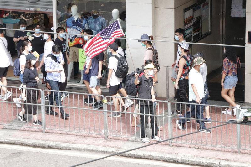 港區國安法生效後的第一個「七一」紀念日,民眾自發上街,在銅鑼灣崇光百貨一帶等多個地點進行抗議示威,其中有人舉起美國國旗。香港國安法對勾結境外勢力明訂刑責。中央社記者張謙香港攝 109年7月1日