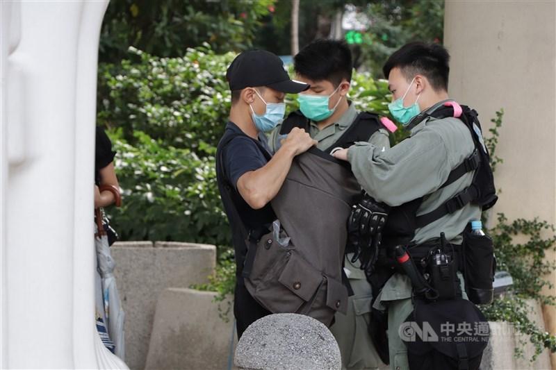 「港區國安法」效力範圍大,組織「台獨」、在台灣犯案都可能適用。一個外國人在外國行使當地的言論自由,主張港獨,在香港也可能會被抓。圖為5月27日防暴警察在灣仔截查可疑示威者。(中央社檔案照片)