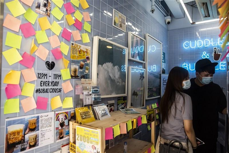 「港區國安法」實施後,香港人頓時面臨因言獲罪的風險,支持民主的港人於是發揮創意用暗語避險。圖為香港一間奶茶店內的「藍儂牆」上貼滿空白便條紙。(法新社提供)