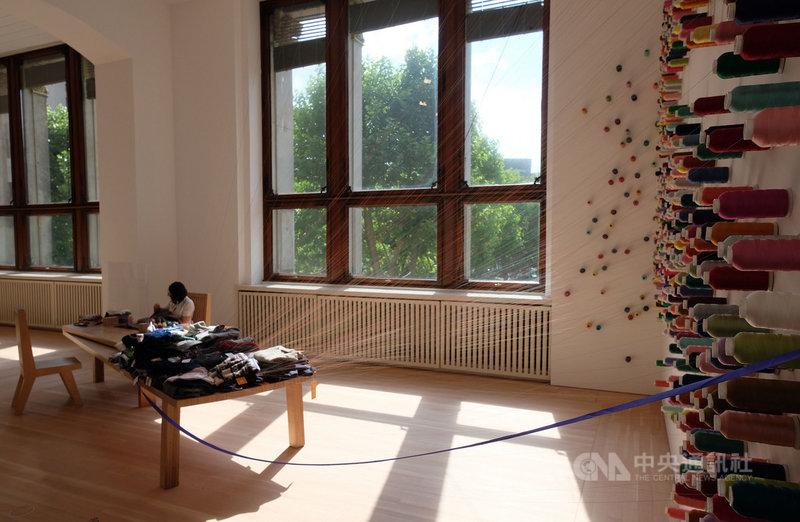 李明維創作之一「補裳計畫」現場有人專心縫製衣物,桌上堆滿縫完但線頭還沒剪斷的衣物,透過細絲與牆上的線軸形成千絲萬縷的連結。中央社記者林育立柏林攝 109年7月8日