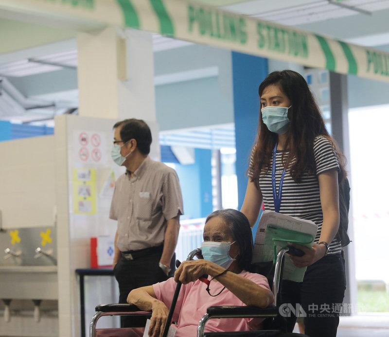 新加坡10日舉行國會大選,將從朝野11個政黨192名候選人中選出93席國會議員。圖為上午8時到12時赴德能中學(Dunearn Secondary School)投票站投票的65歲以上選民。中央社記者黃自強新加坡攝 109年7月10日