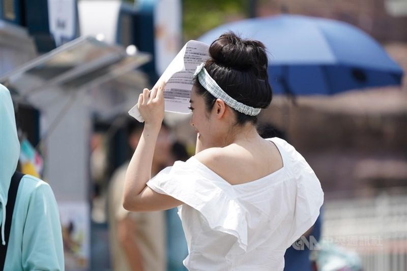 根據中央氣象局觀測,台北測站13日中午11時59分氣溫達到攝氏38.9度,創下歷年7月最高溫紀錄。圖為街頭民眾以物品遮擋豔陽。中央社記者徐肇昌攝 109年7月13日