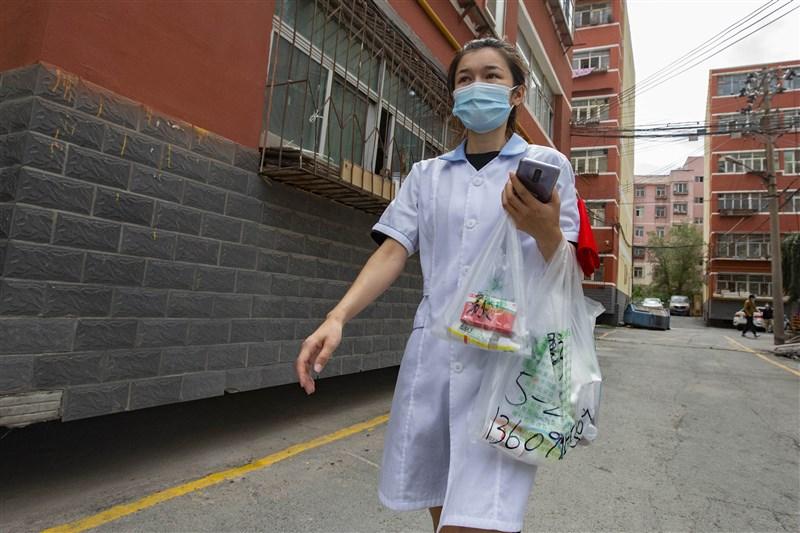 中國12日新增武漢肺炎確診病例19例,其中8例本土病例,都集中在新疆烏魯木齊市。圖為烏魯木齊藥店工作人員為居民配送所需藥品。(中新社)
