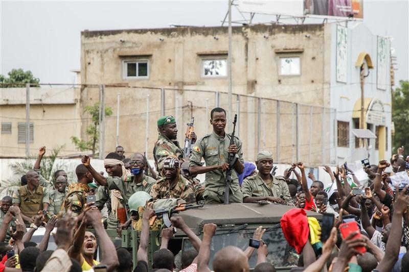 馬利反叛軍人18日發動政變,逮捕總統凱塔和總理席斯。圖為馬利武裝人員行經巴馬科獨立廣場時,受到民眾歡呼。(法新社)