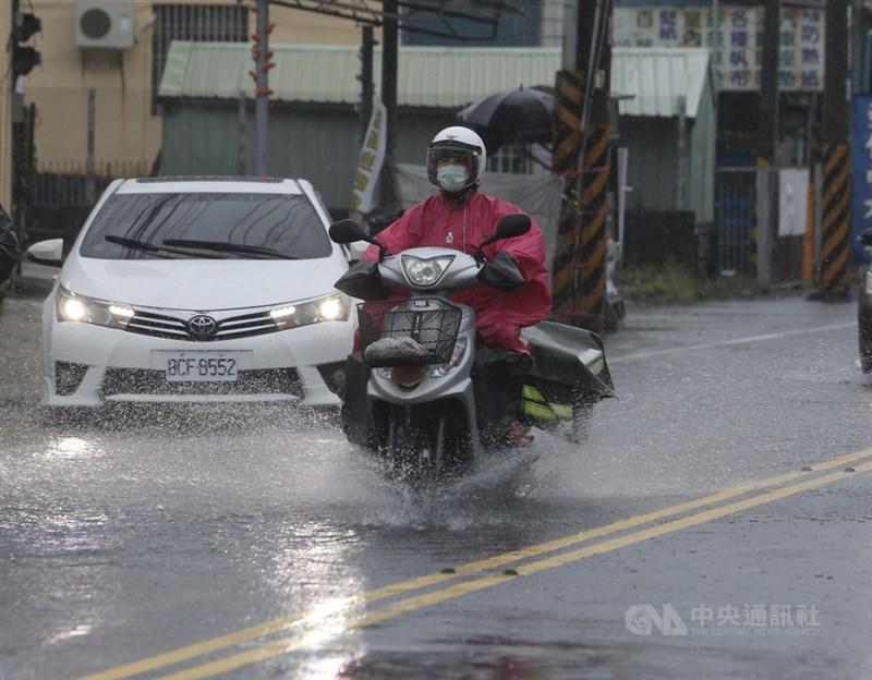 受到西南風影響,南台灣遭雨彈強襲,高雄地區26日強降雨導致多處傳出積淹水災情。圖為民眾騎車行經積水路段,呼嘯而過同時也濺起大量水花。中央社記者董俊志攝 109年8月26日