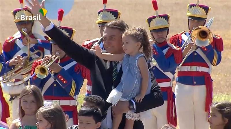 巴西總統波索納洛(中)在總統官邸晨曦宮舉行活動,無視防疫措施,圍在身旁的多位兒童也都沒戴口罩。(圖取自facebook.com/jairmessias.bolsonaro)