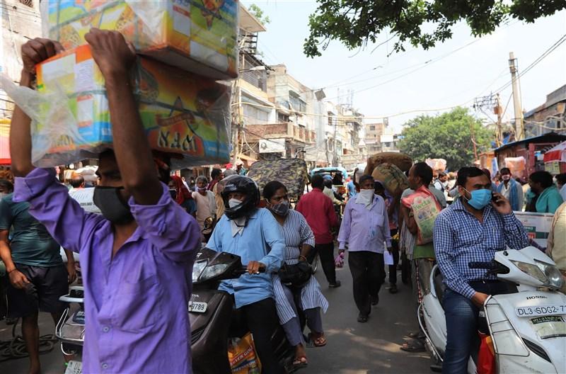 全球武漢肺炎病例數破3000萬大關,北美和南美洲占近一半,不過印度疫情延燒,是最新疫情關注焦點。圖為新德里市場的民眾戴口罩自保。(安納杜魯新聞社)