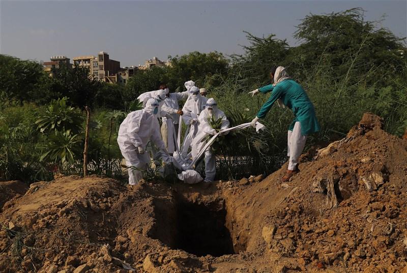 印度聯邦衛生部20日公布的資料顯示,境內過去24小時新增9萬2605起武漢肺炎確診病例,染疫人數飆至540萬。圖為新德里民眾埋葬因武漢肺炎病逝的家人。(安納杜魯新聞社)