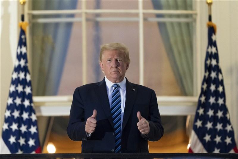 確診武漢肺炎的美國總統川普日6日傍晚出院,隨後搭乘總統直升機返抵白宮,並登上白宮陽台,摘下口罩,雙手比讚。(美聯社)