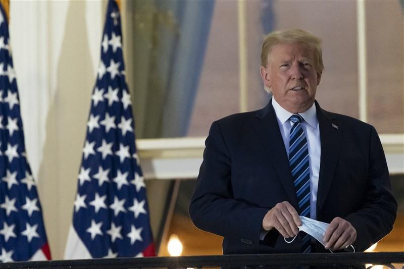 美國總統川普確診武漢肺炎,住院治療4天後於5日出院,他一抵達白宮就摘下口罩。(美聯社)