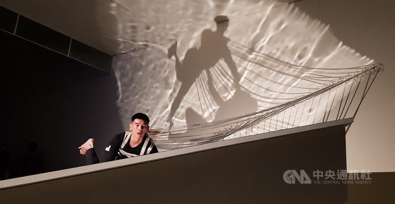舞者周書毅(圖)與藝術家傅雅雯為「禽獸不如—2020台灣美術雙年展」共創的多媒體裝置表演「活著–2020國美館版本」,將24條彈簧固定在周書毅身上,作為延伸身體的24塊脊椎骨,每一個延展動作都隱喻著身體與空間的關係。中央社記者鄭景雯攝 109年10月17日
