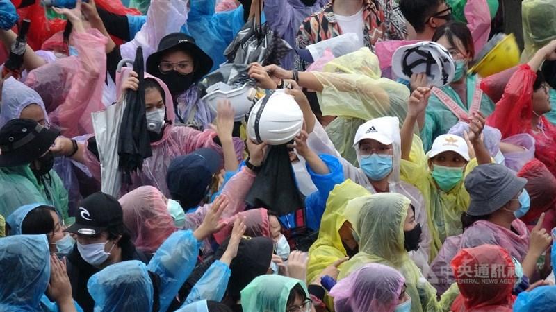泰國反政府示威團體18日號召上萬支持者聚集在勝利紀念碑路口,由於擔心再遭警方驅離發生危險,抗議民眾協助遞送安全帽等物資。中央社記者呂欣憓曼谷攝 109年10月18日