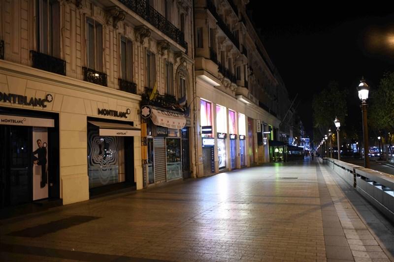 法國確診新型冠狀病毒病例逾3萬2000人,寫下單日新高紀錄,總統下令巴黎與8個城市宵禁今晚生效。圖為17日晚間巴黎街頭一片死寂。(中新社)