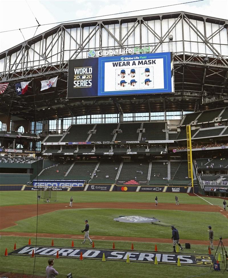 MLB世界大賽開放球迷入場,但人數嚴格管控首戰只有1萬多人進場,寫下百餘年來世界大賽觀眾最少的一次。圖為比賽場地大螢幕提醒觀眾戴口罩。(共同社)