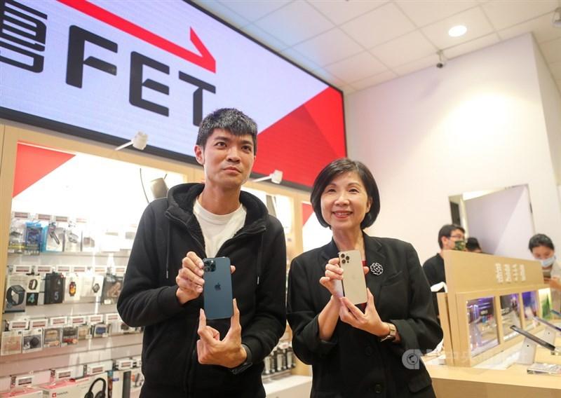 蘋果iPhone 12、12 Pro 23日在台灣正式開賣,搶到遠傳電信頭香的民眾曾先生(左)拿到到新機後,與遠傳電信總經理井琪(右)合影留念。中央社記者裴禛攝 109年10月23日