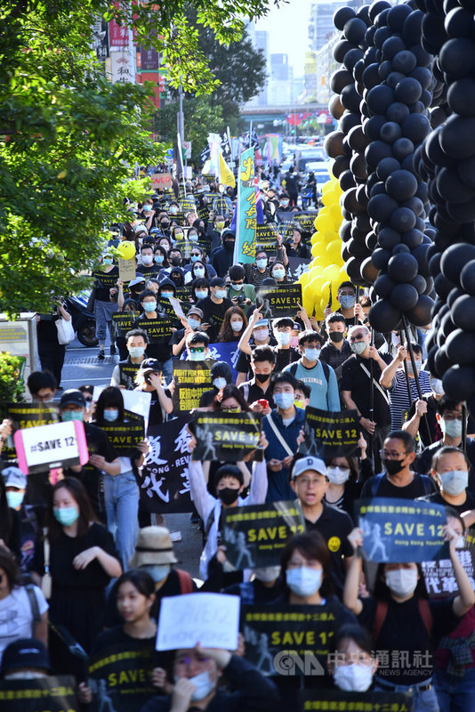 1025台灣撐港遊行25日下午在台北登場,參與民眾手持黑底黃字標語前進,不時呼喊「釋放12港人」、「光復香港、時代革命」等口號。中央社記者王飛華攝 109年10月25日